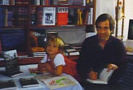 Tommy Hays signs books with one of his children nearby
